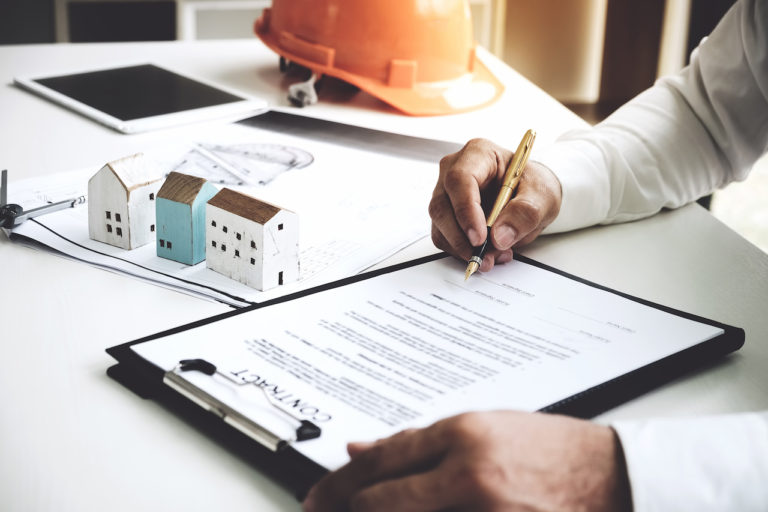 a man filling out forms attached to a clipboard, with an orange hard hat in the background