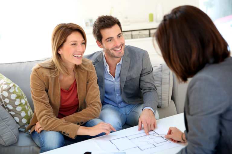 a couple reviewing plans and contracts with a saleswoman in a suit. They are seated on a sofa and the plans are on a coffee table in front of them