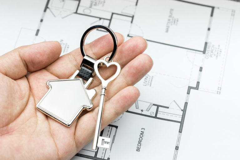 a hand holding a set of house keys above some plans. The key ring is solver and shaped like a house, the top of the large silver key is a heart shape.